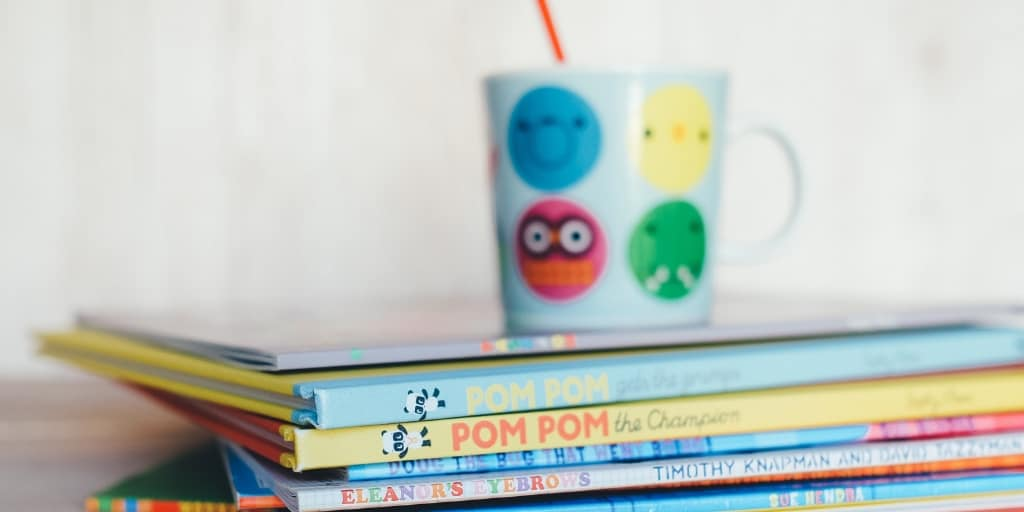 stack of kids books with kid cup on top