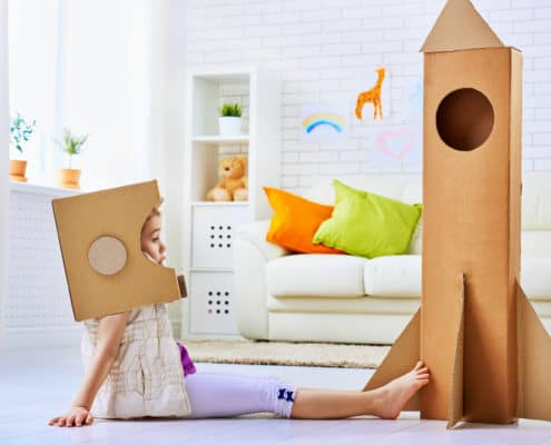 girl kid with cardboard astronaut helmet on, facing cardboard space ship she created
