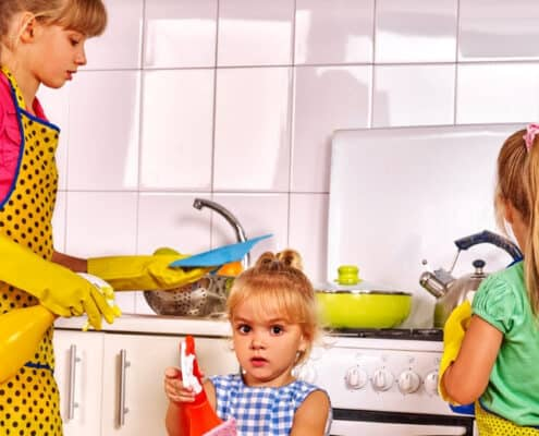 three kids with chic aprons, doing chores for allowance