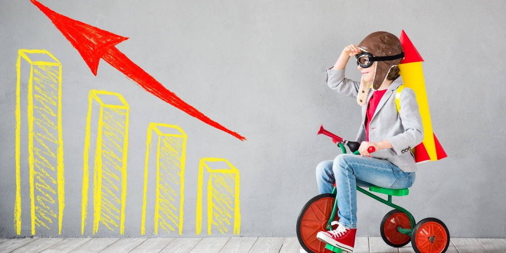 boy kid on a bicycle with a business chart on his left, looking to the future of kids business games
