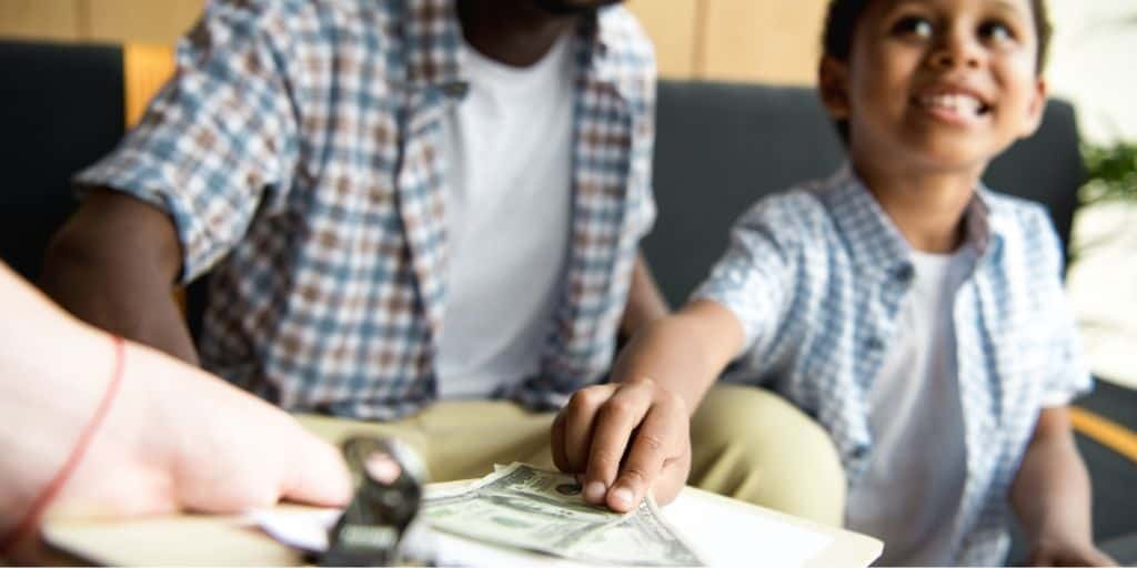 man with son in restaurant, letting son hand over money to waitress
