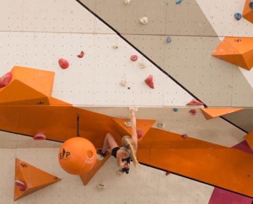 young woman on a rock climbing wall, climbing