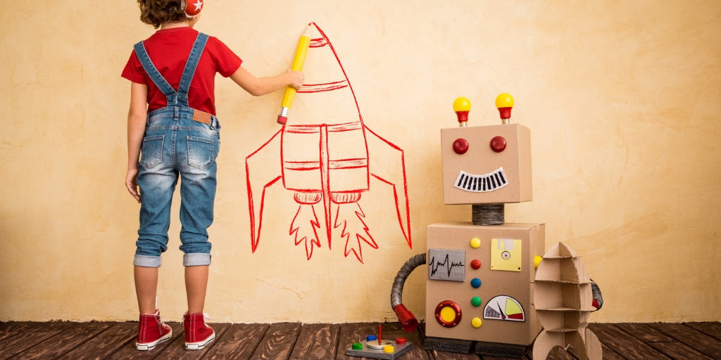 boy child with a cardboard robot, drawing a spaceship on the wall