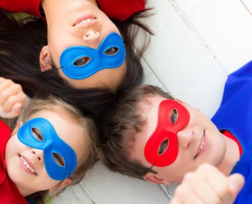 Family of three wearing superhero costumes, working on family financial goals