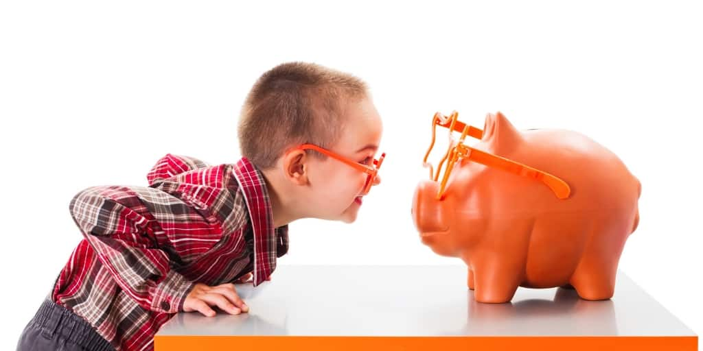 boy with orange glasses staring at an orange piggy bank with orange glasses