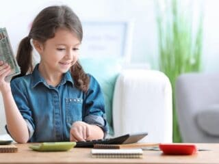 young girl with hand of money and smiling, using calculator at desk
