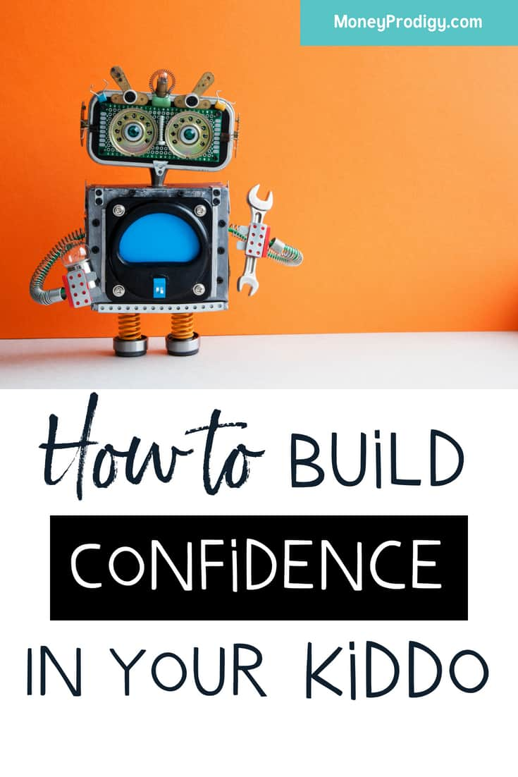 """robot standing on white desk, orange background, text overlay """"how to build confidence in your kid"""""""