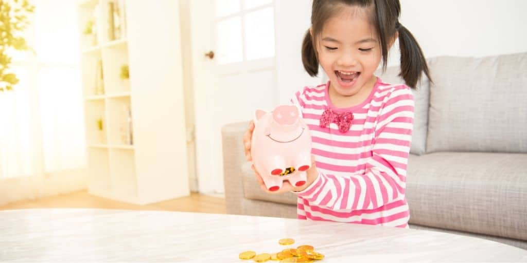 young child excitedly spilling her piggy bank contents onto table