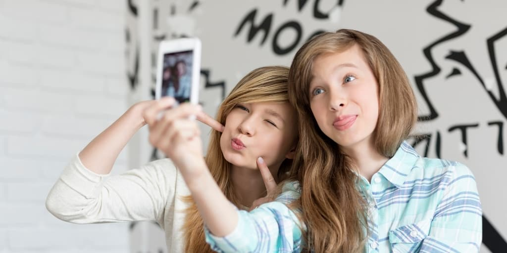 two teen girls taking a silly selfie on a phone