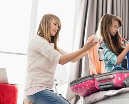 two kids folding laundry to do chores off their chore list