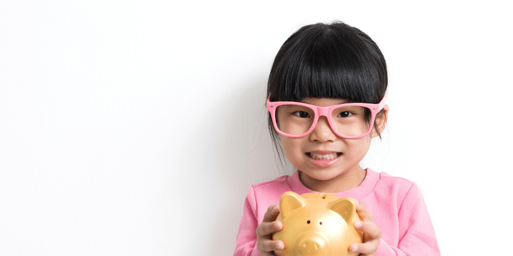 little girl with pink glasses holding a piggy bank, waiting for personal finance homeschool lessons