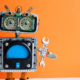 robot standing on white desk, orange background, building tools
