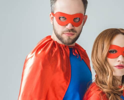 mother and father in superman outfits, on grey background