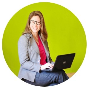 image of author Amanda L. Grossman on laptop, wearing glasses and business suit