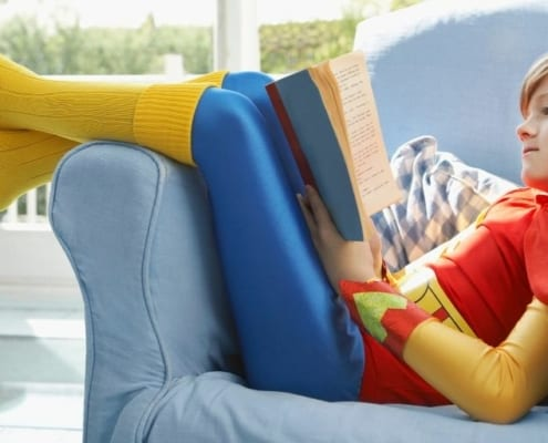 child in superman outfit on couch reading books about money for kids