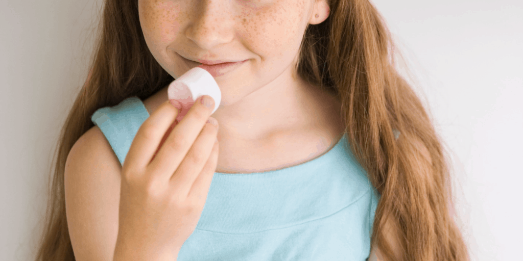 Girl holding a marshmallow to her mouth, looking like she might eat it, with a smile