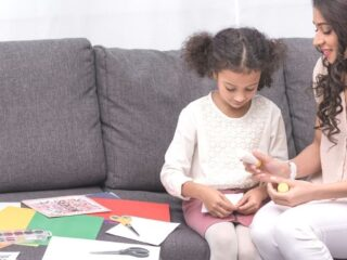 mother with young daughter, helping her glue together and make a vision board for kids