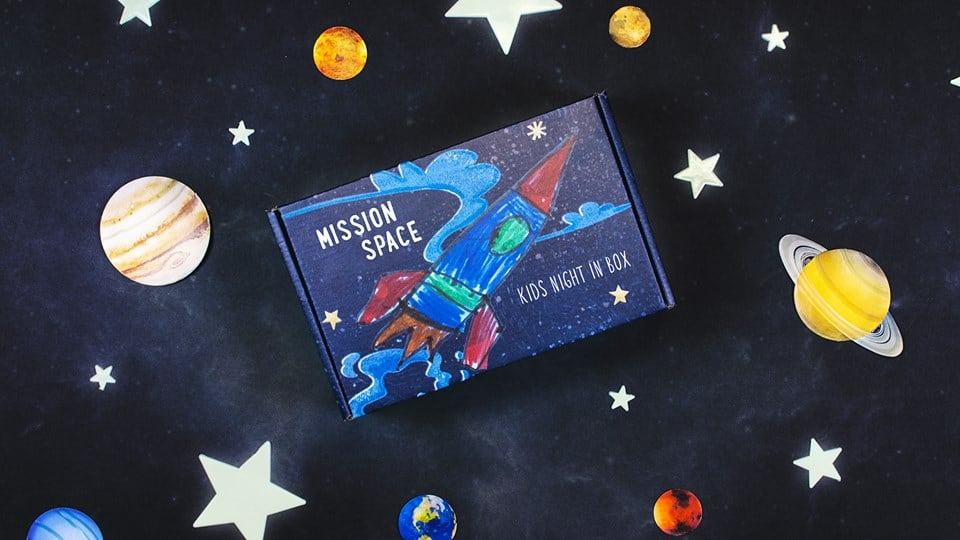 box with a rocket ship on it drawn by a kid, with stars and planets on background