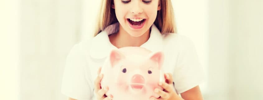tween girl holding a pink piggy bank and excited for allowance for kids