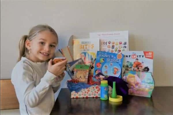 learning crates kid subscription box review with a young girl, next to bubbles and books