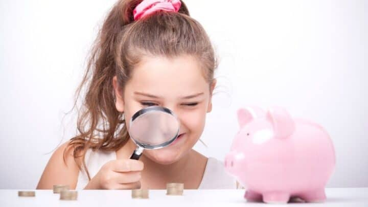 tween girl with magnifying glass looking at money and piggy bank