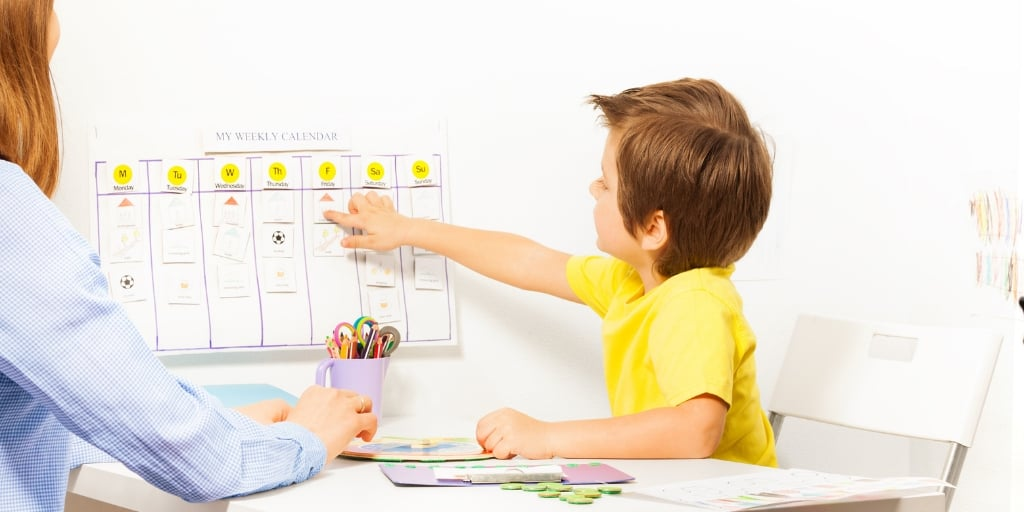 mother with child in yellow shirt, child pointing to chore chart for kid