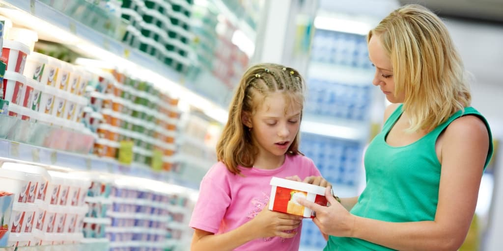 Daughter and mother in store aisle, daughter asking mother to buy her something