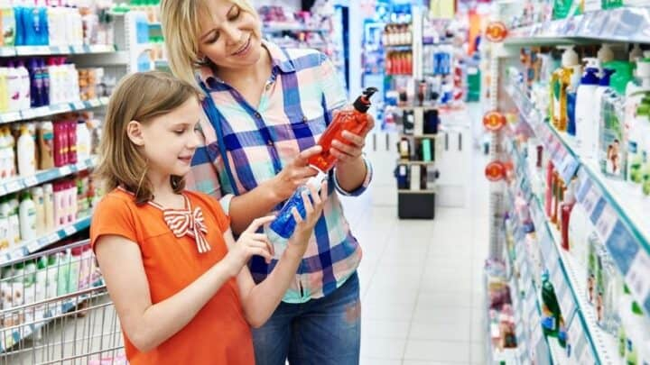 mother and daughter doing grocery store money challenge, looking at product bottles
