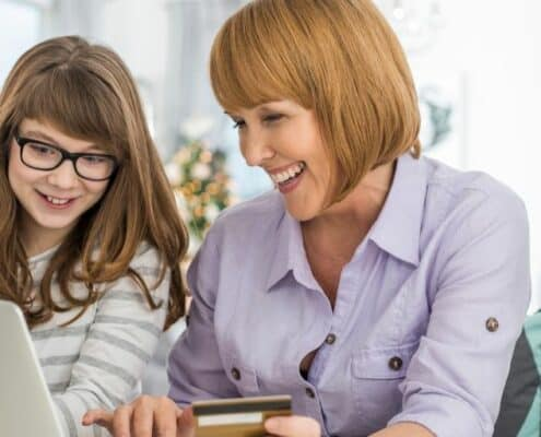 mother and daughter with glasses on laptop, making purchase with credit card