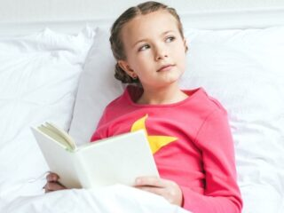 young girl kid in bed reading business book for kids, looking off into distance