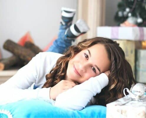 teenage girl laying on floor in front of gifts - amazon gifts for teenage girl