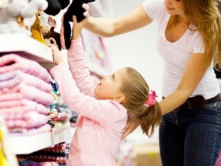 mom and daughter at store, daughter choosing something to buy