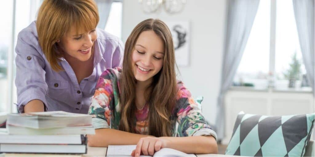 mother leaning over teen or tween daughter, reading investing books for kids