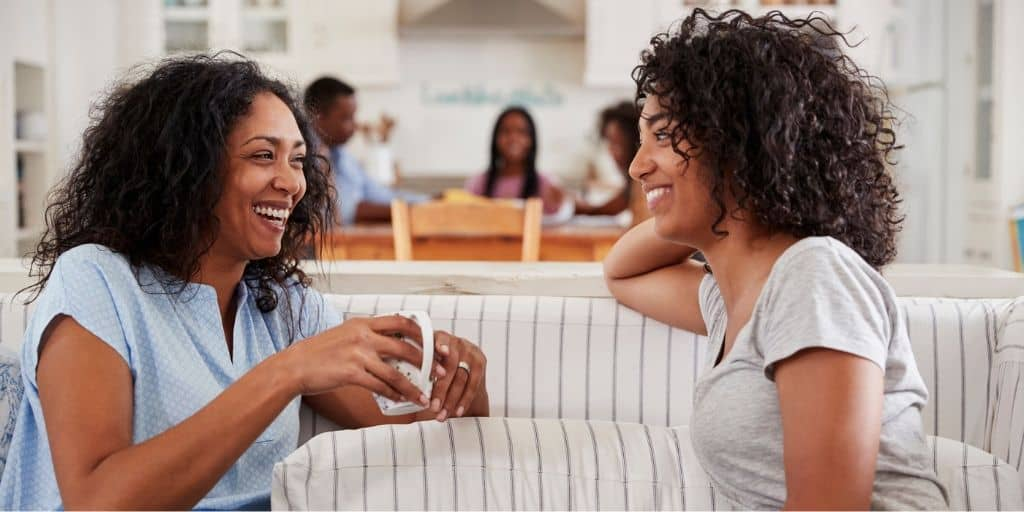 mother and daughter on couch, talking about first paycheck - teenager