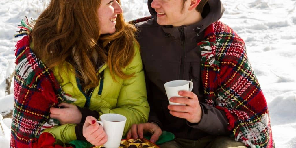 teenage couple with chocolate and hot cocoa, enjoying cute valentine's day date ideas