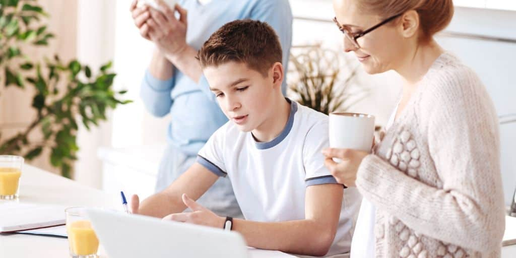 mother helping teenage son fill out sample budget template for teenager