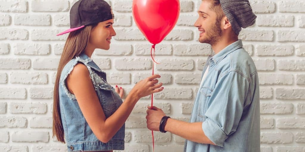 teenage couple holding a red balloon, girl giving high school valentines day gifts for him