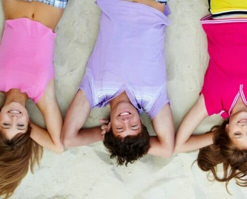 three teenagers laying on their backs, smiling, thinking about what to spend money on as a teenager