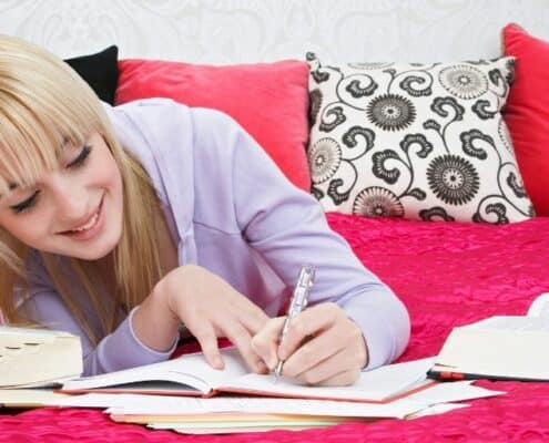 teenage girl on pink bed working on goals