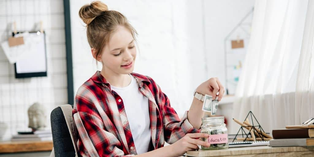 teen girl putting money in a mason jar, figuring out how to save money as a teen