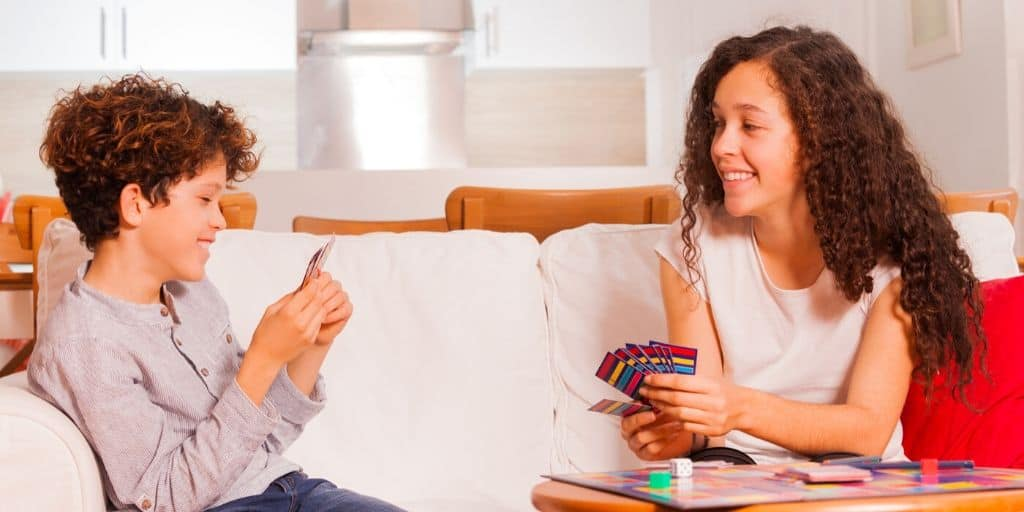 kids playing a fake money game together on the couch, smiling