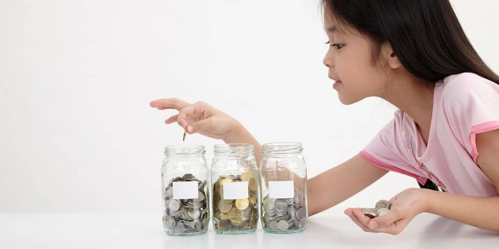 young Asian girl counting coins in three jars