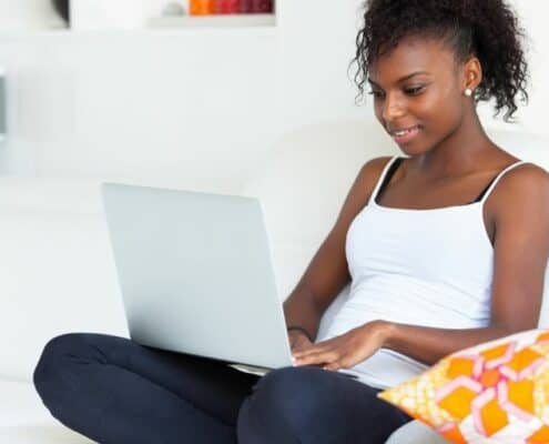 teenage girl with laptop in lap, on couch, using apps that pay teens