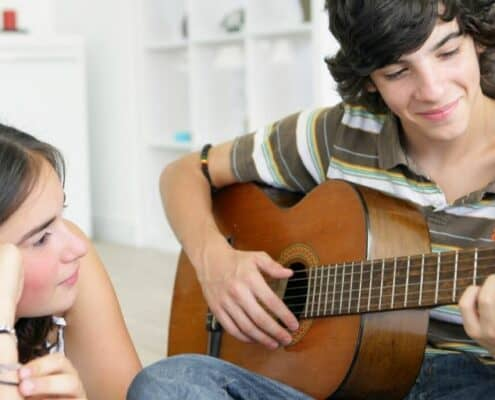 teenage couple on at home date night, teen boy playing his guitar