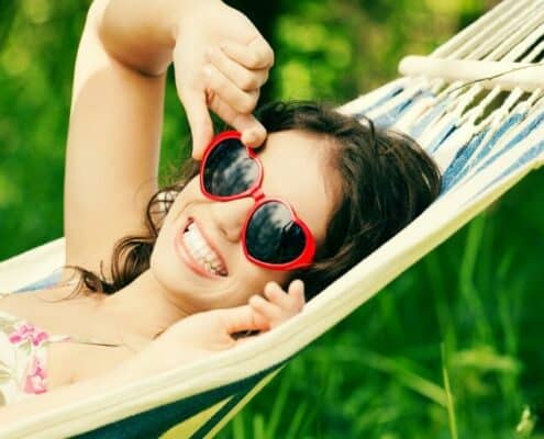 teen girl with sunglasses, on hammock, doing summer teen activities