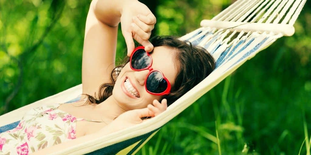 teen girl with sunglasses, on hammock, doing summer teen activities