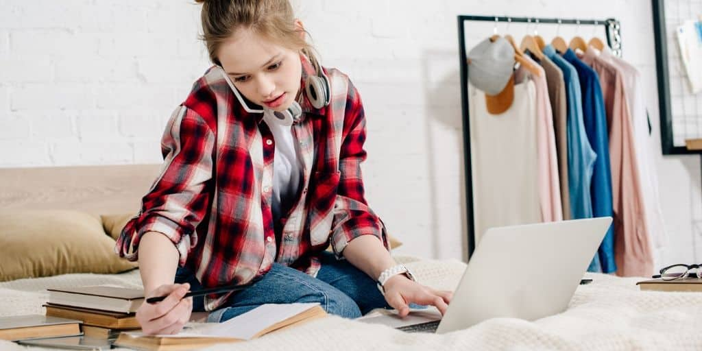 young teen working on a business plan for students worksheet on her bed, with laptop, books, and while on phone