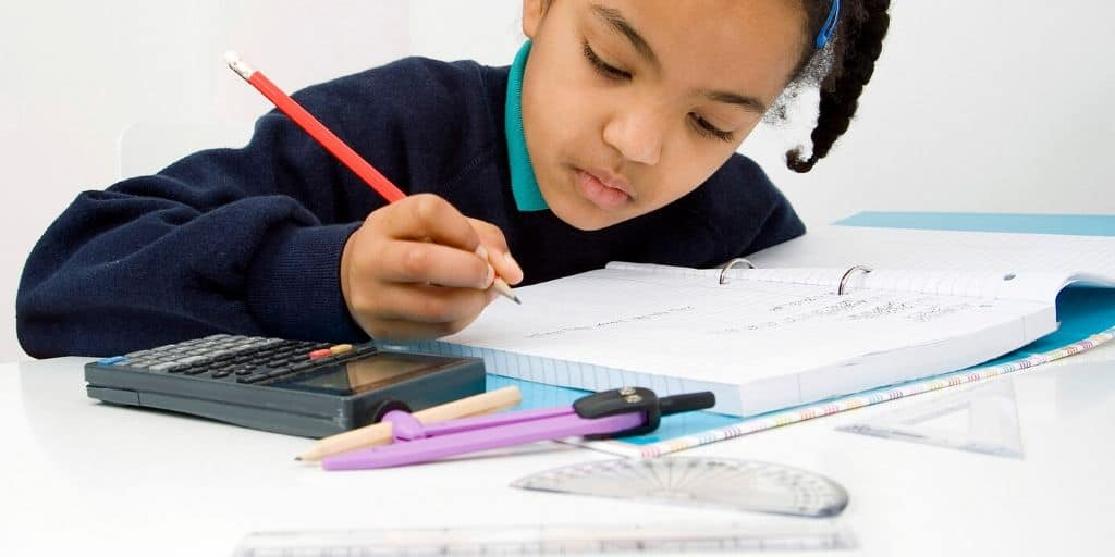 young child working on a stock market worksheet pdf at a desk, with calculator and pencil