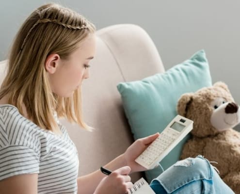 teen student sitting on couch working on goal setting worksheets for teens pdf