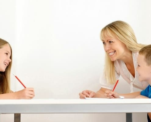 mother helping teach kids about investing at table, boy and girl